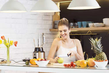 Young woman cutting fruit in the kitchen