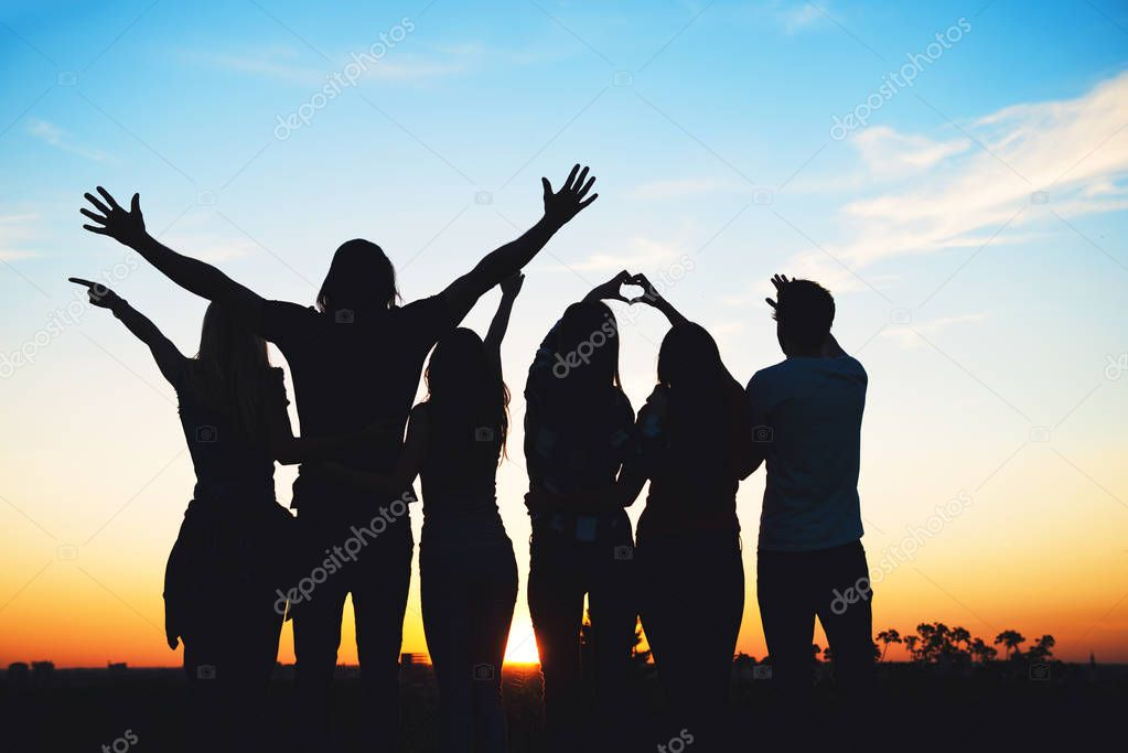 Group of people having fun outdoors at sunset