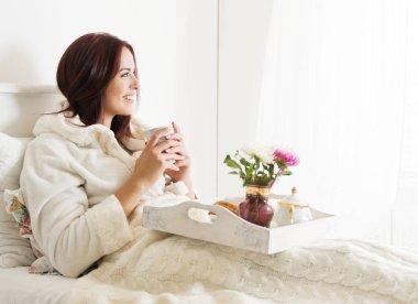 Beautiful woman laying and enjoying, breakfast in bed