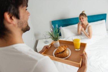 Man bringing breakfast to his girlfriend in bed