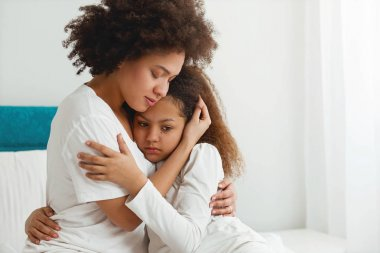 Mother comforting her daughter, sitting in the bedroom, hugging