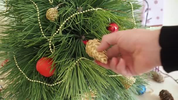 Man decorates a Christmas tree.