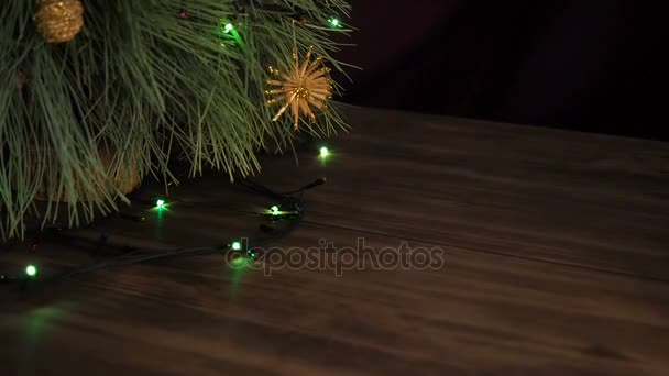 The man puts box of gift under the Christmas tree. Fir stand on the wooden table and decorated with glowing garland and Christmas toys.
