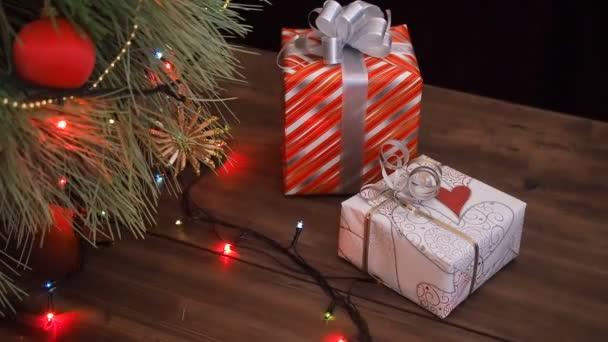 Jsou pole dárků pod stromeček. Dárky jsou zabaleny v barevných papíru a svázané s řetězec a stuhy. Vánoční věnec na větve stromů jedle. Větve stromů blízko, posunout pohybem, panorama