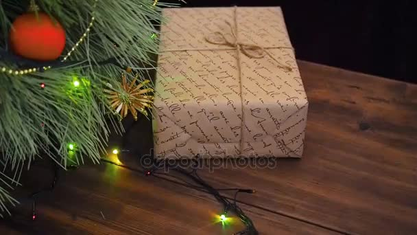 Box of gifts are under the tree. Gift are Packed in broun paper and tied with twine. Christmas garland on the fir tree branches.