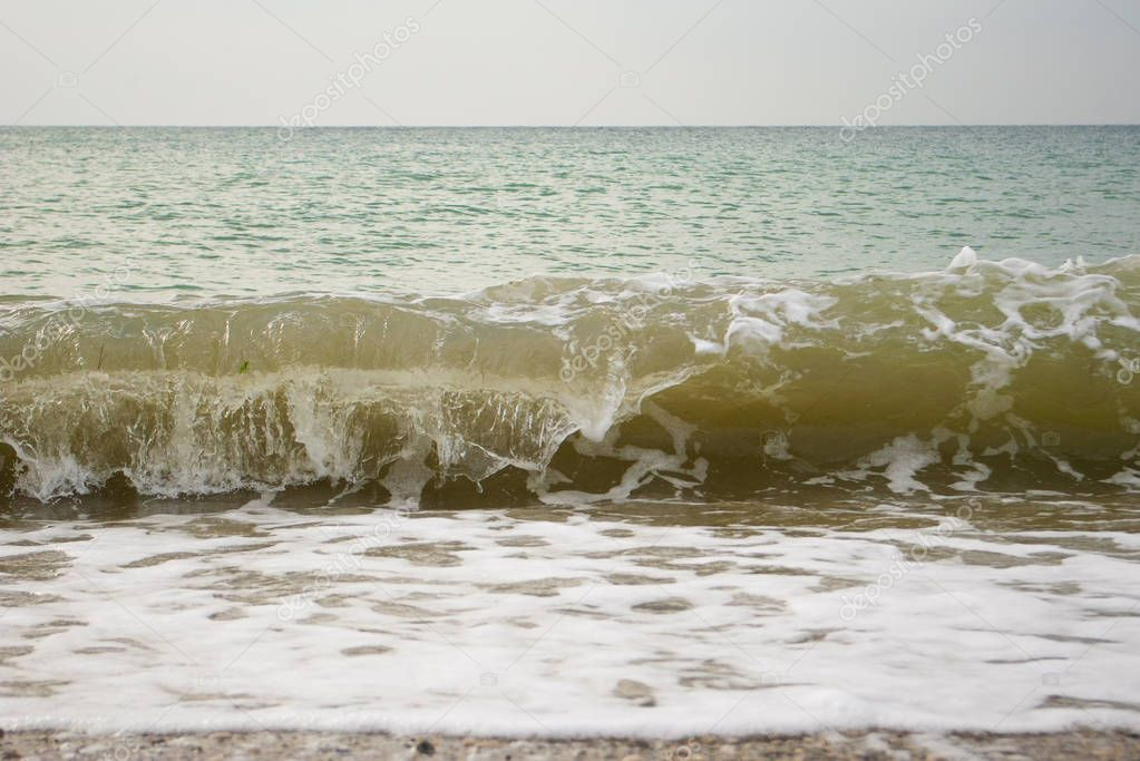 Foaming waves on the seashore, close-up. Seascape in cloudy day