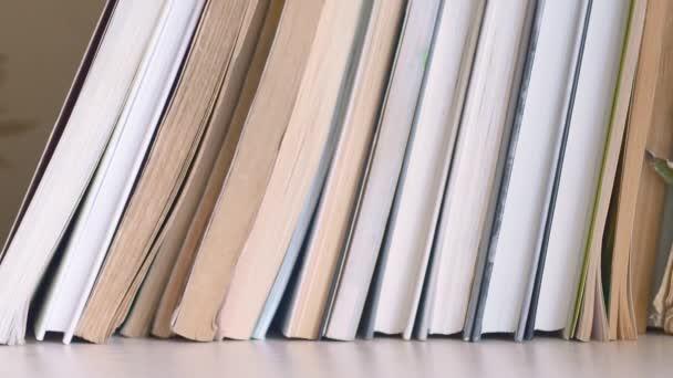 Dolly klouzala po polici s knihami a pohybovala se zleva doprava. Vedle těch nových stojí staré knihy s potrhanými stránkami. Knihy jsou na poličce s knihami..