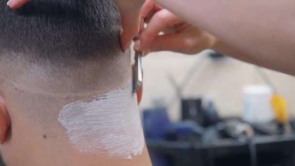 Stylist Rasieren Männchen Nacken mit offenem Rasiermesser, Nahaufnahme. Rasiermousse auf dem Nacken der Kunden. Mann im Friseurladen. selektiver weicher Fokus. verschwommener Hintergrund.