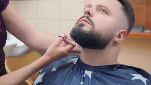 Stylist schneidet Männchen Bart mit Schere, Nahaufnahme. männlich im Friseursalon. aufgenommen im Friseursalon. selektiver weicher Fokus. verschwommener Hintergrund.