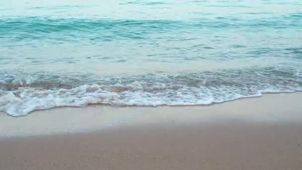 Rudé moře vlny tekoucí po hnědé písečné pláži, střední střela. Přírodní pozadí. Vyfoceno v Hurghadě v únoru. Selektivní měkké zaměření. Rozmazané pozadí.