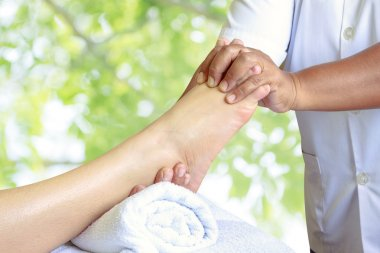 Masseur doing reflexology,Thai foot massage in spa on nature bac