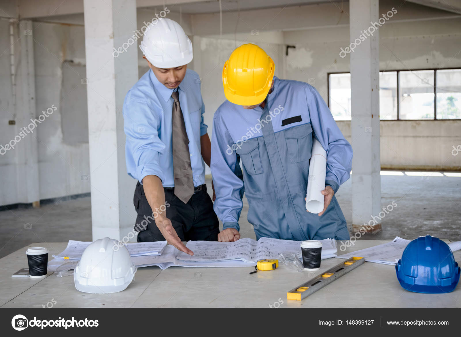Engineers and foreman working with blueprint on construction sit engineers and foreman working with blueprint on construction sit stock photo malvernweather Image collections