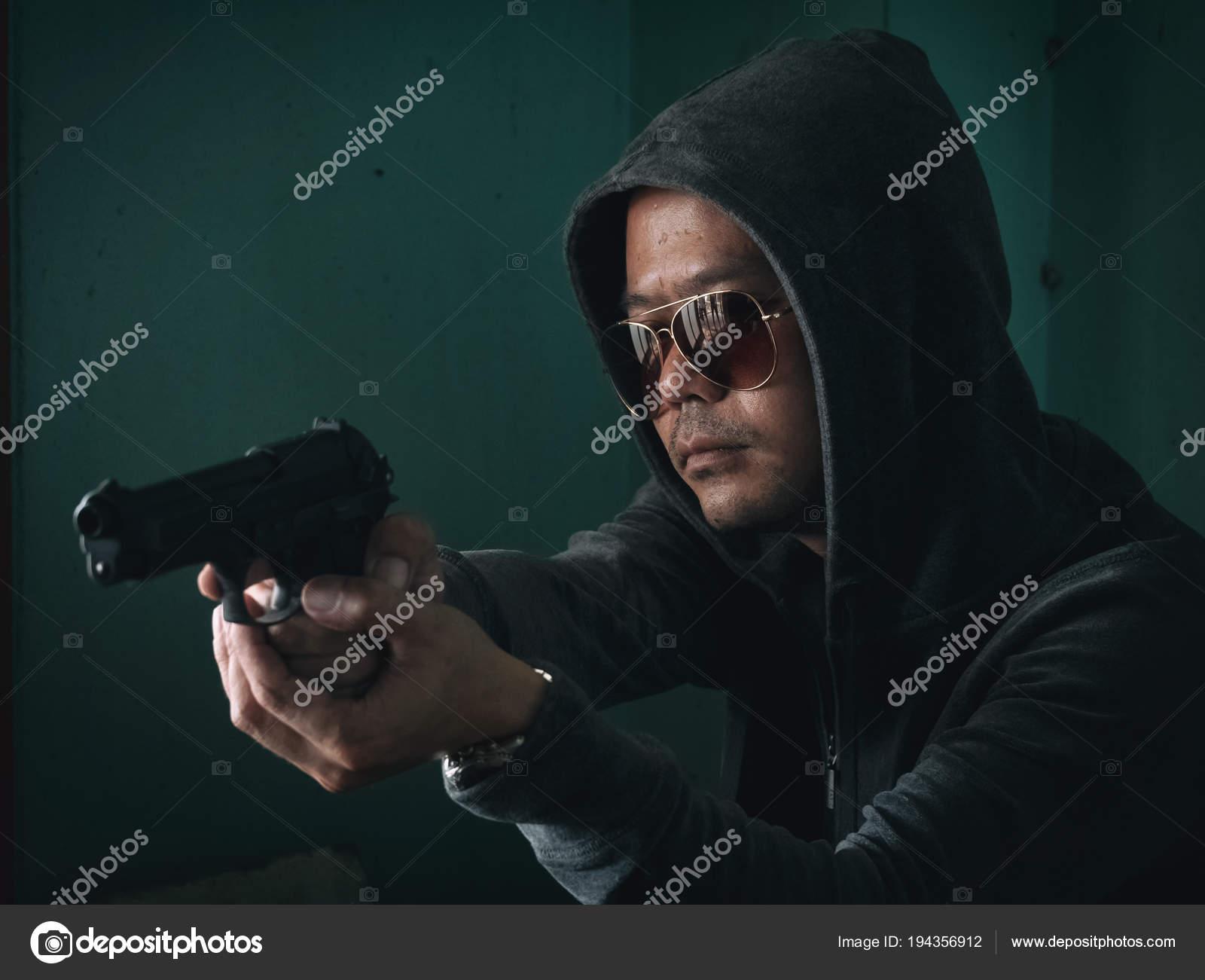Hombre encapuchado con un arma en el cuarto oscuro — Foto de stock ...