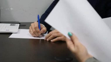 Office life concept. Close up of hands signing papers. Shot in 4k