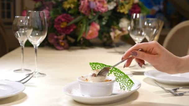 Restaurant interior. Saint Valentines Day. Dessert with icecream and fresh fruit. Female hand with spoon eating. Shot in 4 k