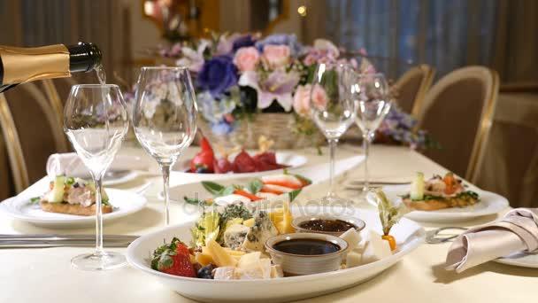 Restaurant-Innenraum. Valentinstag. Tisch in einem Restaurant. Teller mit Käse in der Mitte. Nahaufnahme. Champagner ins Glas gießen. Zeitlupe