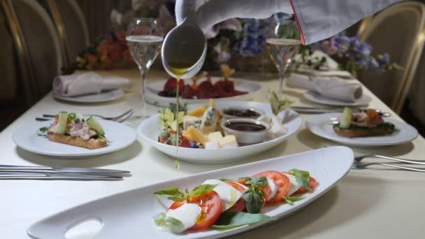 Zdravé potraviny a vegetariánské pojetí. Zblízka se vylévání obsahu olivového oleje nad salát caprese. Italské caprese salát s mozzarellou. Zpomalený pohyb