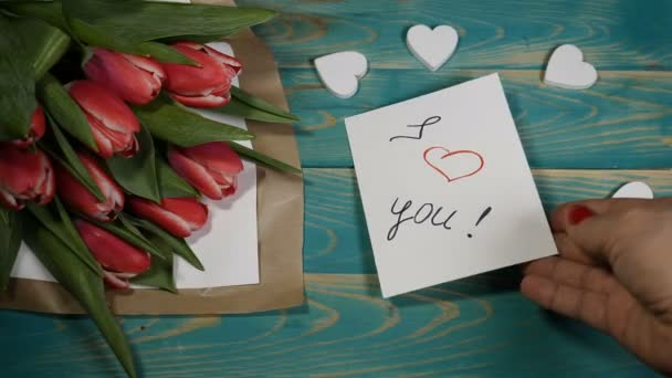 Top view of a I love You message note and Tulips flowers bouquet on a wooden table. Love relationship concept. St Valentine s Day. Shot in 4 k