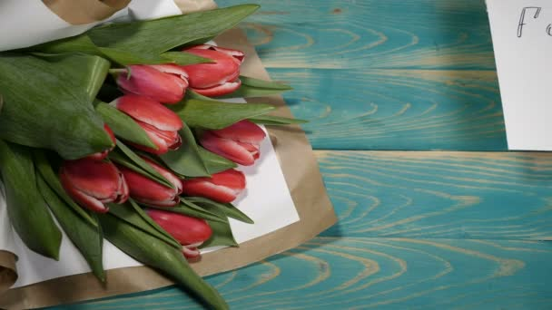 Top view of a forgive me message and Tulips flowers bouquet on a wooden table. Couple relationship concept. Shot in 4 k