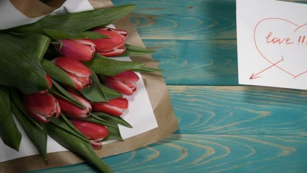 Pohled shora láska zprávy poznámky a kytice tulipány na dřevěný stůl. Milostný vztah koncept. St s Valentýna. Snímek v rozlišení 4 k