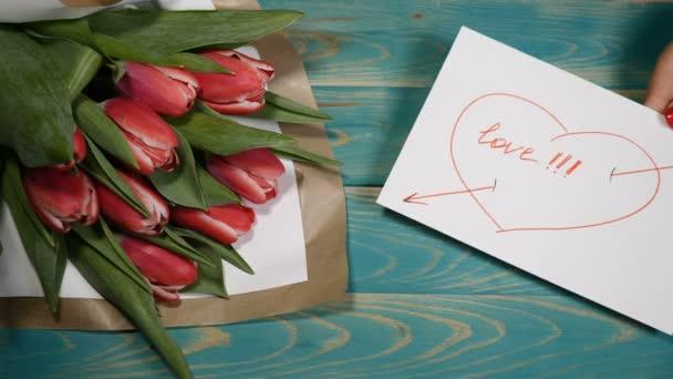 Top view of a I Need You message note and Tulips flowers bouquet on a wooden table. Love relationship concept. Saint Valentines Day. Shot in 4 k