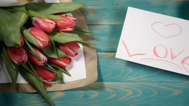 Felülnézete a szerelem üzenet Megjegyzés és a tulipán virágok csokor egy fából készült asztal. Szerelmi kapcsolat fogalmát. Szent Valentin-nap. Shot 4 k