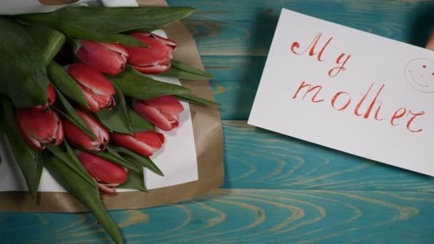 Pohled shora moje matka zprávy poznámky a kytice tulipány na dřevěný stůl. Milostný vztah koncept. Den matek. Snímek v rozlišení 4 k