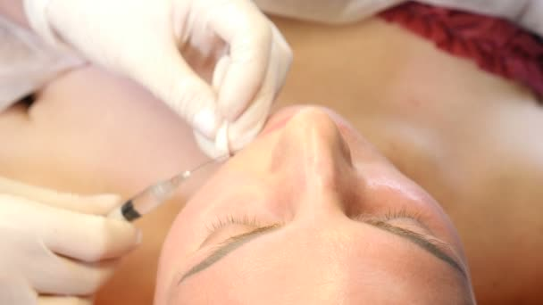 Beauty clinic concept. Close-up of beautician hands making botox injection to female lips. Young woman gets facial injection procedur.. Facial rejuvenation. 4k