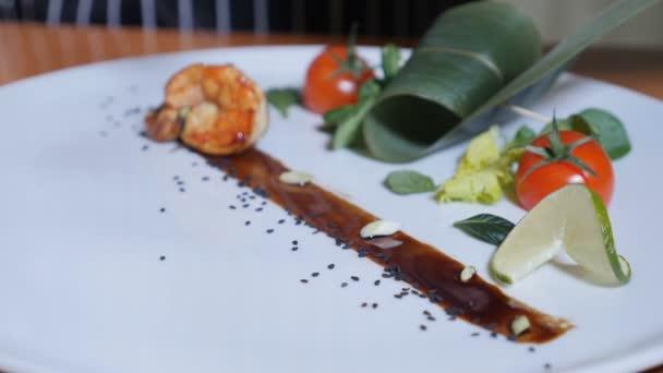 Közeli kép: a szakács, Flambe stílusban edényt a tigris garnéla egy tányérra. Lassú mozgás. Olaj- és alkohol gyullad nyitott. Full hd
