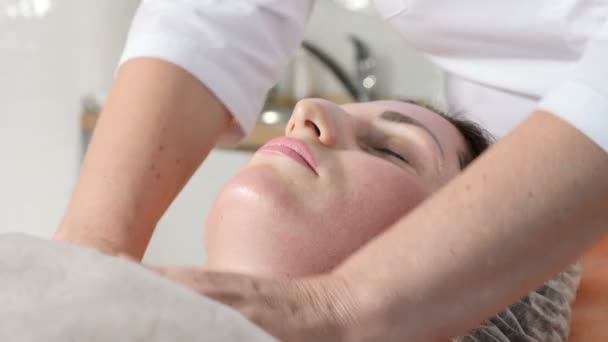 Skin care concept. Close up of Beautician making facial massage preparing client face skin for botox injection. Facial rejuvenation. Shot in 4k
