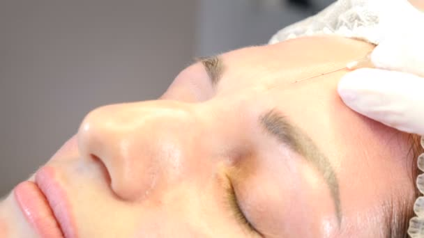 Beauty clinic. Beautician hands in gloves making face aging injection to a female skin. A woman gets beauty facial cosmetology procedure. botox injection to female forehead. collagen injections. Shot