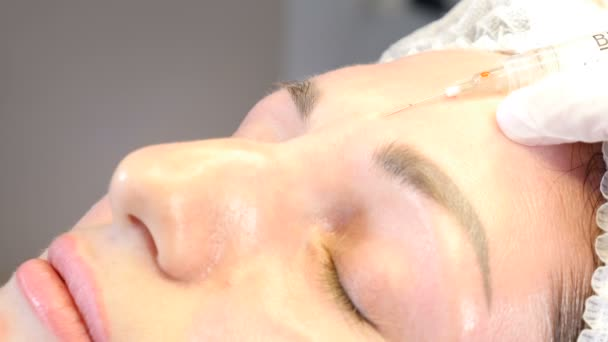 Beauty clinic. Beautician hands in gloves making face aging injection to a female skin. A woman gets beauty facial cosmetology procedure. botox injection to female forehead. collagen injections. 4k