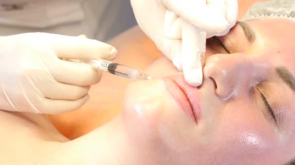 Beauty clinic koncept. Detail ruce kosmetičky botox injekce do ženské rty. Mladá žena dostane obličeje injekce. Omlazení obličeje. Snímek v rozlišení 4k