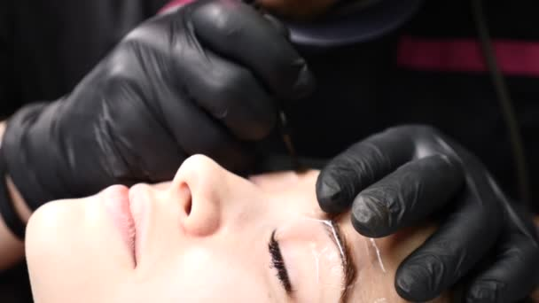 Kosmetický salon. Zblízka se mužské kosmetičky v černých rukavicích takže permanentní make-up postup na ženský obočí. Mladá žena dostane obličejové kosmetické procedury. Omlazení obličeje