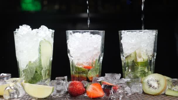 Bar- und Cocktailkonzept. Barkeeper bereiten verschiedene Mojito-Cocktails zu. Nahaufnahme. Spritzer. Zeitlupe.