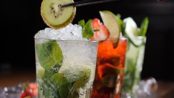 Final Touch-Konzept. Bar und cocktail-Konzept. Barkeeper bereiten verschiedene Mojito Cocktails. Hautnah. Ein Stück von Qiwi auf Glas mit Cocktail hinzufügen. Slow-motion