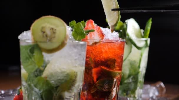 Final-Touch-Konzept. Bar- und Cocktailkonzept. Barkeeper bereiten verschiedene Mojito-Cocktails zu. Nahaufnahme. Hinzufügen einer Scheibe Limette auf dem Glas mit Cocktail. Zeitlupe.