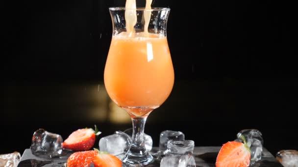 Bar- und Cocktailkonzept. Barkeeper bereiten Fruchtcocktails zu. Barmann gießt Saft in Glas mit Eis. Nahaufnahme. Spritzer. Zeitlupe.