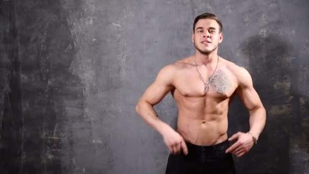 starker muskulöser Mann auf schwarzem Hintergrund erschossen, der auf den leeren Raum links von ihm zeigt und lächelt.