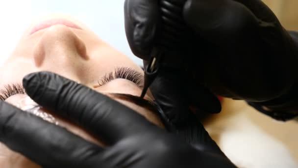 Salone di bellezza. Chiuda in su del maschio estetista in guanti neri, rendendo la procedura di trucco permanente sopracciglia femminili. La giovane donna ottiene procedura di bellezza del viso. Ringiovanimento del viso. Utilizzando la macchina del tatuaggio