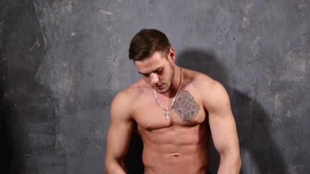 Erős és izmos férfi testépítő. Ember pózol egy fekete háttér, a mutató szép Abs és a mellkasi izmok.