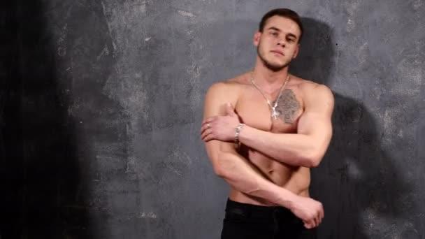 Silné a sval muž kulturista. Muž pózuje na černém pozadí, ukazuje své svaly, krásné Abs a hrudní svaly