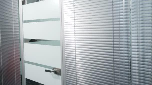 Obchodní kancelář splácení, mužské pracovník otevírá sklo kliku. Muž v obleku dostane mimo prostor otevírání dveří v moderní kanceláři. Snímek v rozlišení 4 k