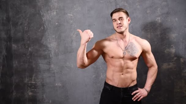 Strong and Muscular man bodybuilder. Man posing on a black background, shows his muscles pointing at empty space beside him to write a note. beautiful ABS and chest muscles.