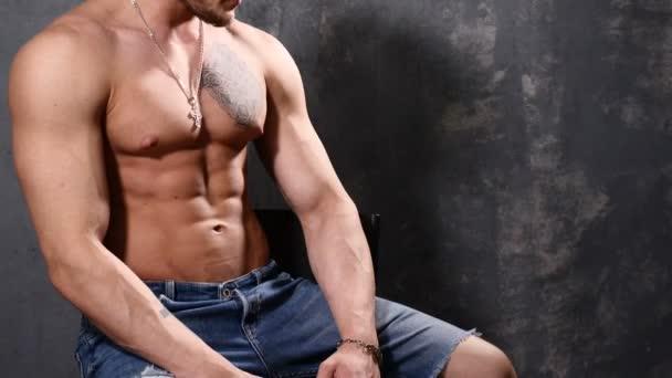 starker und muskulöser Mann Bodybuilder. Mann posiert auf schwarzem Hintergrund und zeigt seine Muskeln. schöne Bauch- und Brustmuskeln.