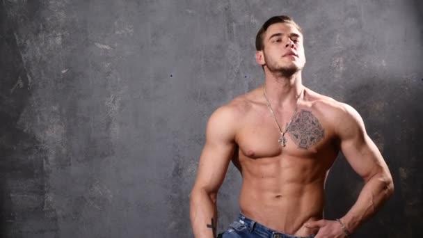 Erős és izmos férfi testépítő. Ember pózol a fekete háttér előtt, azt mutatja, az izmait. gyönyörű Abs és a mellkasi izmok.