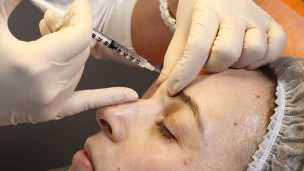 Beauty clinic. Beautician hands in gloves making face anti-aging injection in a female forehead . A woman gets beauty facial cosmetology procedure. Botox. collagen injections