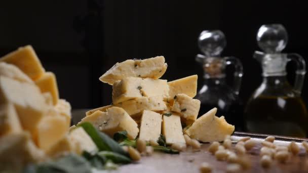 Restaurace art koncept. Různé druhy sýra dát do hromady na černém pozadí. Hrst piniových oříšků v pomalém pohybu