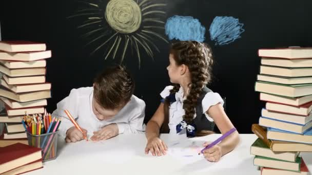 Modern school concept. Boy and girl sit at a desk with heaps of books. and a blackboard behind them. Kids are in class on blackboard background. Pupils busy writing and drawing