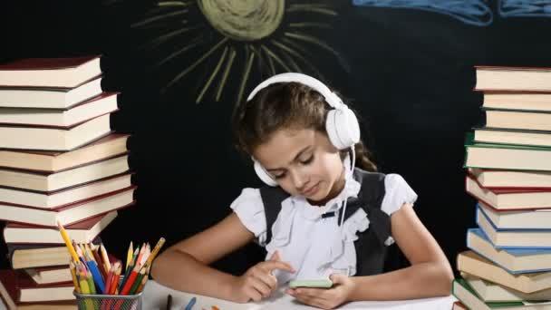 Modern iskola fogalmát. A vonzó lány ül az asztalon halomba rak-ból könyv. és egy tábla mögött őt a gyerek a tanulás osztály tábla háttér. Lány hallgatja a zenét és a szörfözés internet